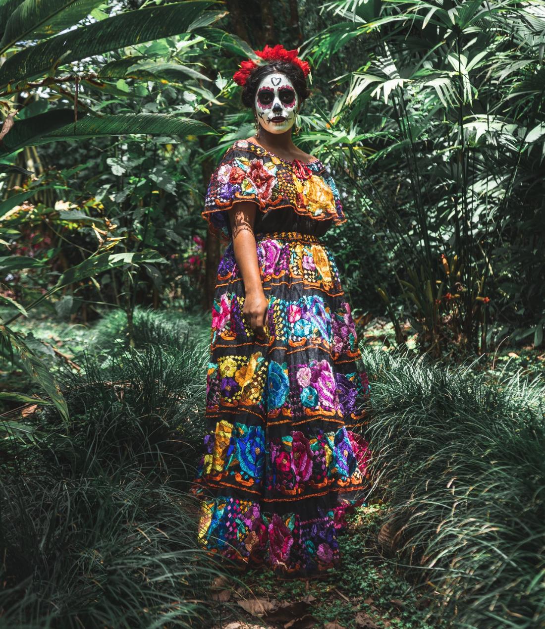 Femme maquillée et venue d'une robe très colorée pour célébrer El Dia de Muertos au Mexique