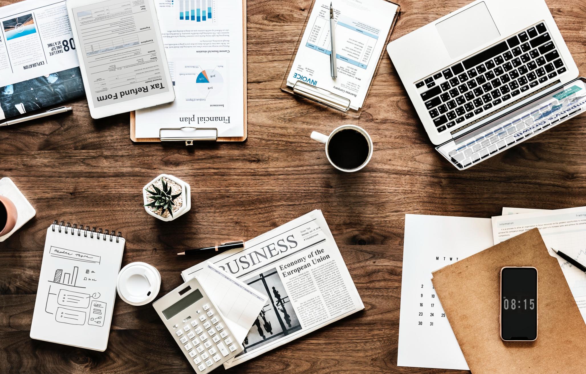 Table de travail avec ordinateur, journaux, business
