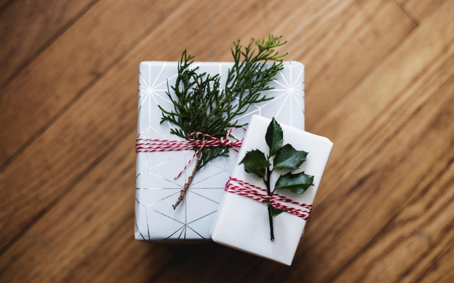 Deux cadeaux emballés simplement avec ruban et branche de sapin